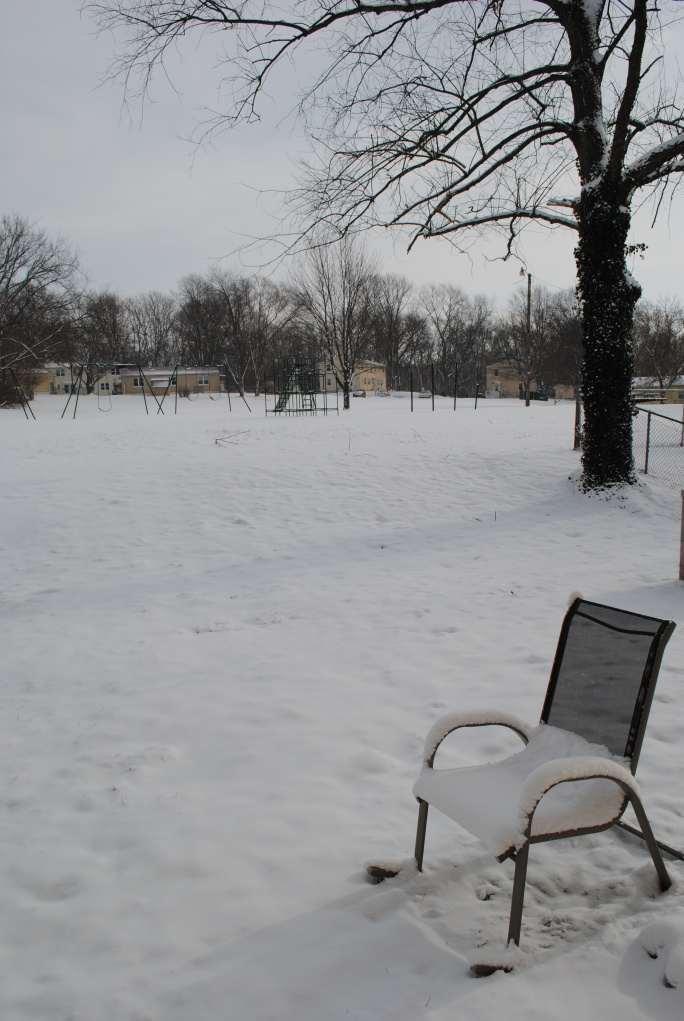 view of snow coved yard, lawn chair, and play ground equiptment